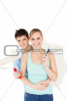 Cheerful couple painting a room