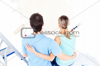 Affectionate couple painting a room
