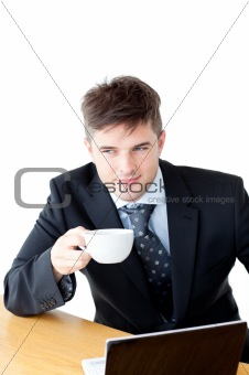 Attractive businessman holding a cup of coffee in front of his l