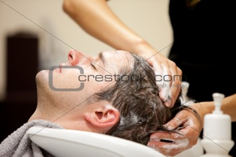 Attractive man having a shampoo