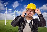 Hard Hat Wearing Engineer on Phone with Turbines Behind
