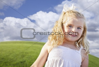 Adorable Blue Eyed Girl Playing Outside in the Grass.