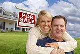 Happy Couple Hugging in Front Yard with Real Estate Sign and House.