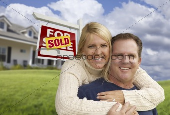 Happy Couple Hugging in Front Yard with Sold Real Estate Sign and House.