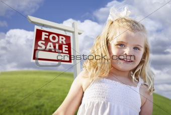 Adorable Smiling Girl in Grass Field with For Sale Real Estate Sign Behind Her.