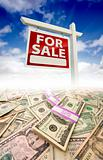 Stacks of Money Fading Off and For Sale Real Estate Sign Against Blue Sky with Clouds.