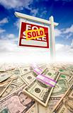 Stacks of Money Fading Off and Sold For Sale Real Estate Sign Against Blue Sky with Clouds.