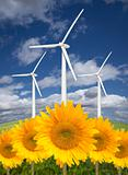 Wind Turbines Against Dramatic Sky, Clouds and Bright Sunflowers in the Foreground.