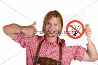 Smiling Bavarian man in lederhose holds no-smoking-rule sign