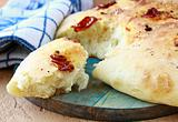 Italian Focaccia bread with tomatoes on a cutting board