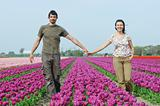 In Tulip Field. Happy young couple in tulips field