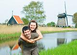 In Tulip Field. Happy young couple near Dutch mills