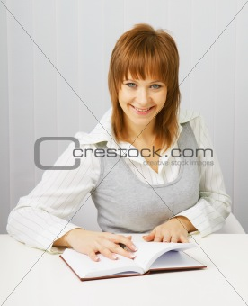 Attractive girl in a white blouse with a notepad and pen