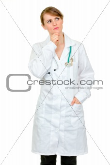 Thoughtful medical doctor woman looking  up at copy space