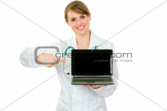 Smiling  medical doctor woman pointing finger on  laptop with blank screen