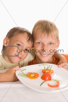 beautiful boys holding a plate with vegetables