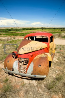 Abandoned Car in Field Under Blue Sky