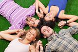 Young People Lying on Green Ground with Hands Joined