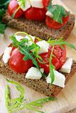 sandwich with mozzarella and tomatoes on rye bread of Italian style