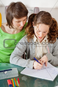 Girl doing homework with her mom