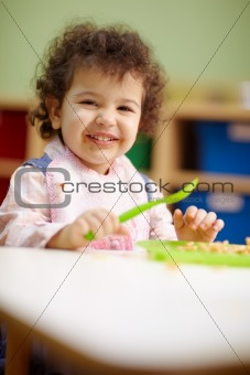 little girl eating lunch in kindergarten