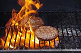 Hamburgers on a flaming BBQ