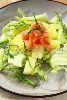 potato salad with smoked salmon and arugula on a plate