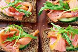 Sandwich with smoked salmon and arugula on a wooden board