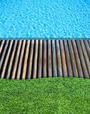 wood floor and fresh grass beside the blue swimming pool