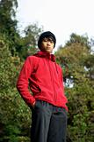 Confident asian man outdoors in red, vertical portrait