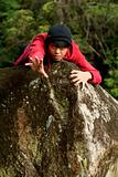 Asian chinese man stretching arm over rock wearing red sweater and beanie