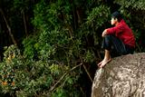 Lonely asian man sitting on rock outdoors wearing cold apparel looking far away