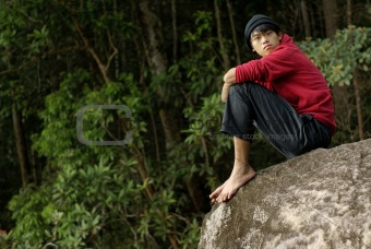 Asian man looking seated on rock outdoors