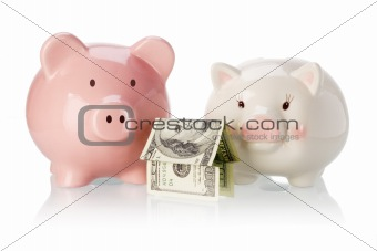 Pair of piggy banks with money house