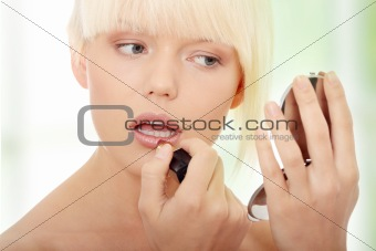 A beautiful young woman applying her make-up