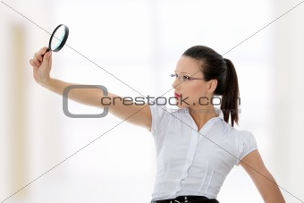 Business woman holding magnifying glass