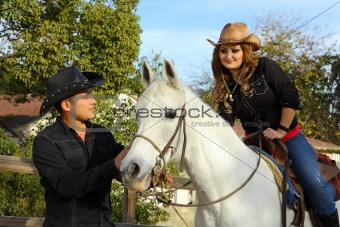 Cowgirl sitting on her white horse