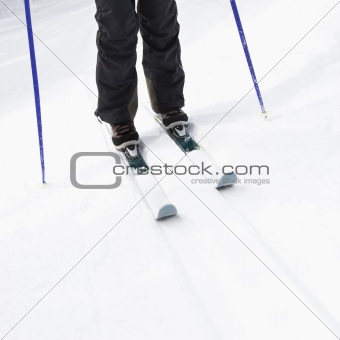 Skier legs on slope.