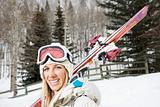 Smiling woman with skis.