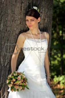 Bride Standing by a tree posing with a bouquet