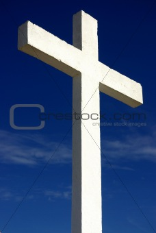 white cross and church against blue sky