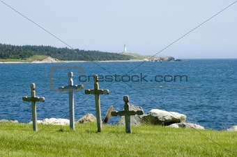Four crosses in cemetary at the edge of the ocean