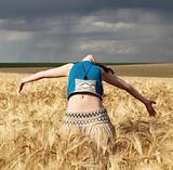 Beautiful girl at wheat field in rainy day.