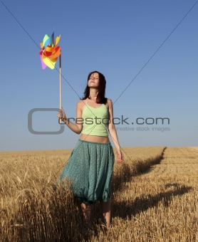 Girl with wind turbine at wheat field