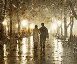Couple walking at alley in night lights. Photo in vintage yellow