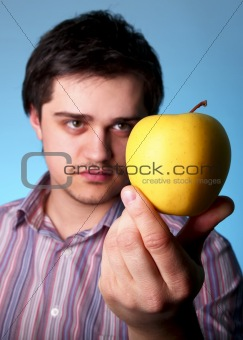 Young men keep yellow apple