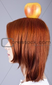 Red-haired girl keep apple on her head. Shot from sideview.