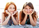 Two beautiful girls lie on the beach.