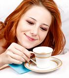 Pretty red-haired sleeping woman in white nightie lying in the bed near cup of coffee.
