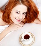 Woman in white nightie lying in the bed near cup of coffee